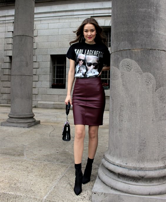 chica de cabello castaño usando una camiseta negra de karl lagerfeld, minifalda de cuero guinda, botines negros estilo sock boots y bolso de mano negro