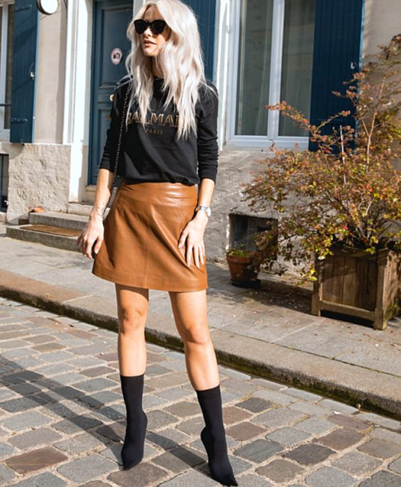Platinum blonde girl wearing sunglasses, black balmain sweatshirt, brown leather mini skirt, black sock boots