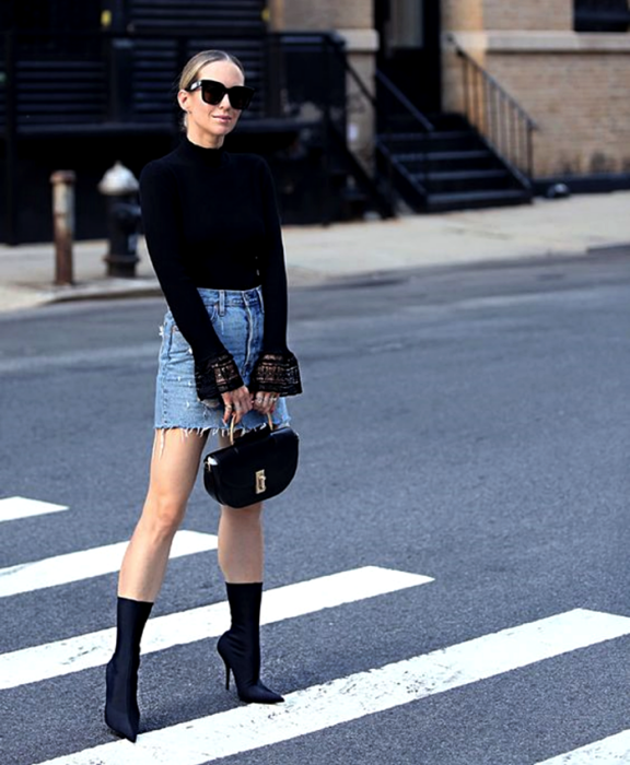 blonde girl wearing sunglasses, black lace long sleeve blouse, denim mini skirt, black clutch bag and black sock boots