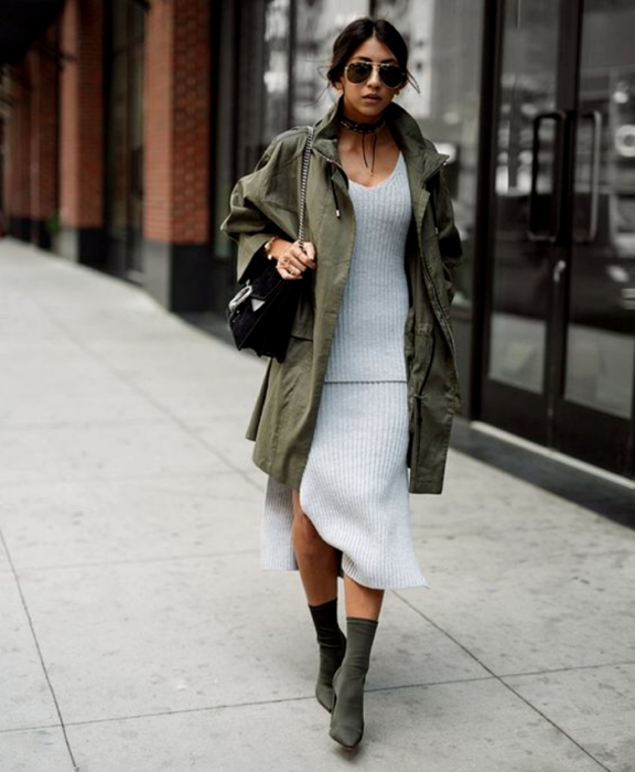 brunette girl wearing sunglasses, gray knit dress, long military green jacket, black handbag and military green sock boots