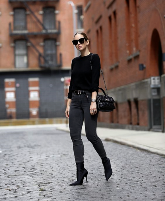 brown haired girl wearing sunglasses, black long sleeve sweater, black skinny jeans, black leather handbag and black sock boot style boots