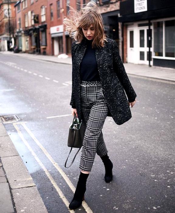 chica de cabello claro usando un top negro, abrigo negro con lunares blancos, pantalones grises de cuadros, bolso negro de mano y botines estilo sock boot negros