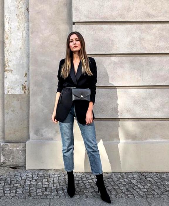 chica de cabello claro largo usando un blazer negro oversized, bolso negro estilo cangurera, jeans rectos y botines negros estilo sock boots