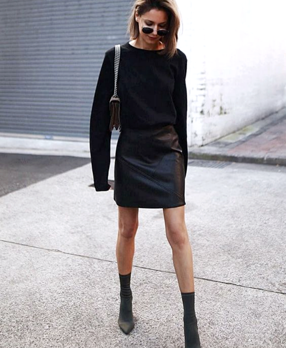 brown haired girl wearing sunglasses, black long sleeve sweater, black leather mini skirt, black chain strap clutch and black sock boots