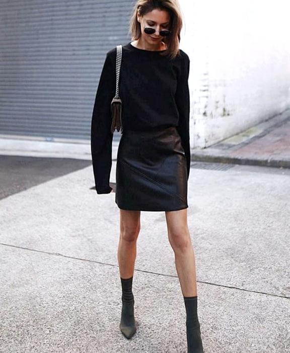 chica de cabello castaño usando lentes de sol, suéter negro de manga larga, minifalda negra de cuero, bolso de mano negro con correa de cadena y botines estilo sock boots negros