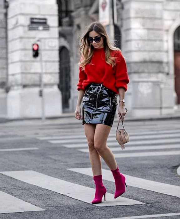 girl with long light hair wearing sunglasses, oversized red sweater, black vinyl mini skirt, fuchsia sock boots and beige handbag