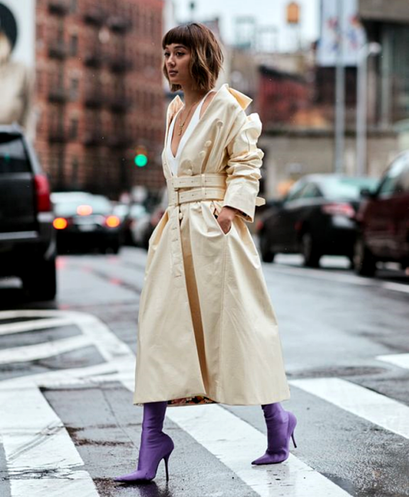 short brown hair girl wearing white tank top, long beige coat, purple satin sock boots
