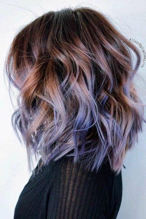 Chica con el cabello rizado en corte bob y teñido en colores morados con rosas