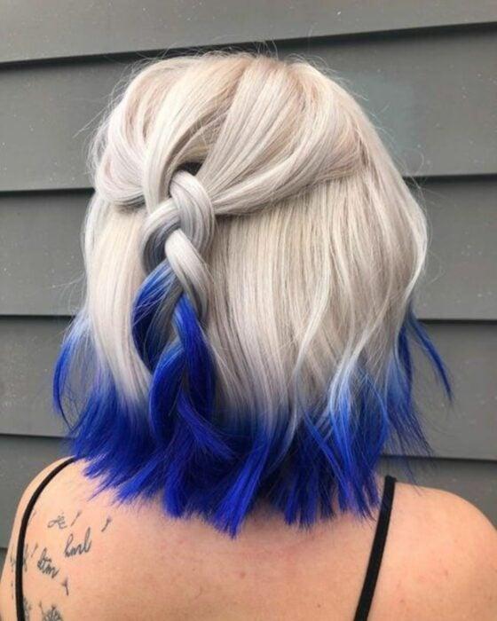 Chica con el cabello hasta la barbilla teñido de color platinado con las puntas en color azul