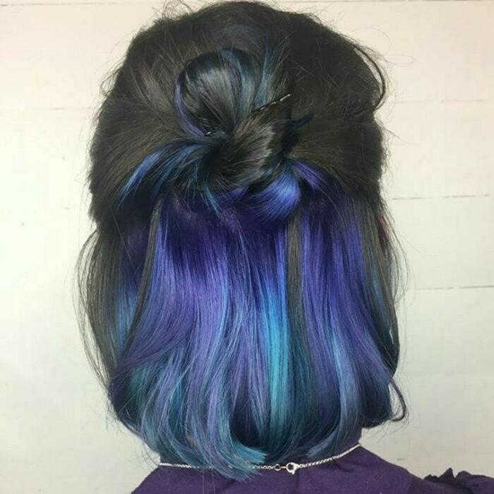Chica con el cabello teñido en color negro con una cortina en color azul