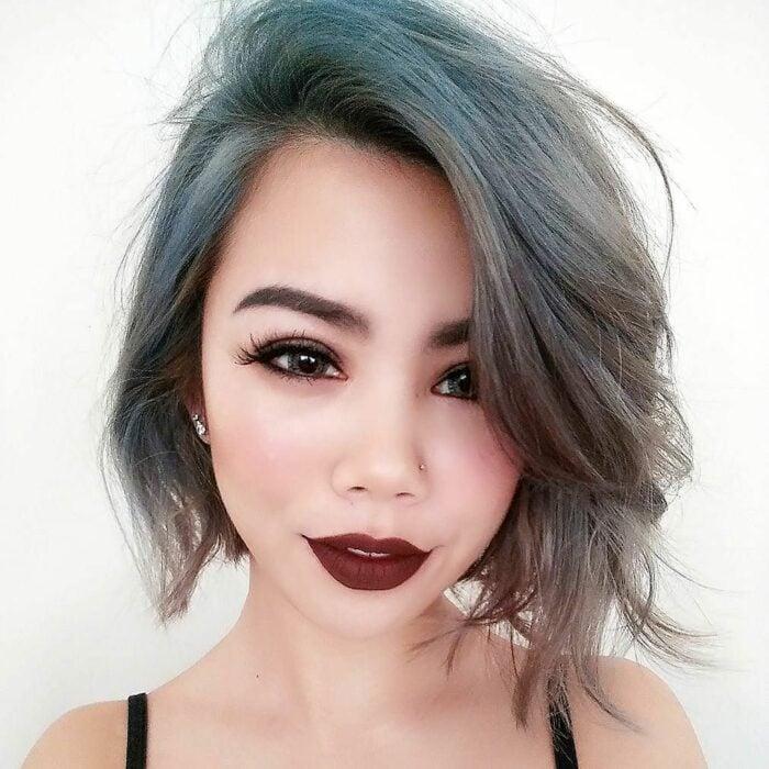 Chica con el cabello hasta la barbilla y teñido de color gris con azul