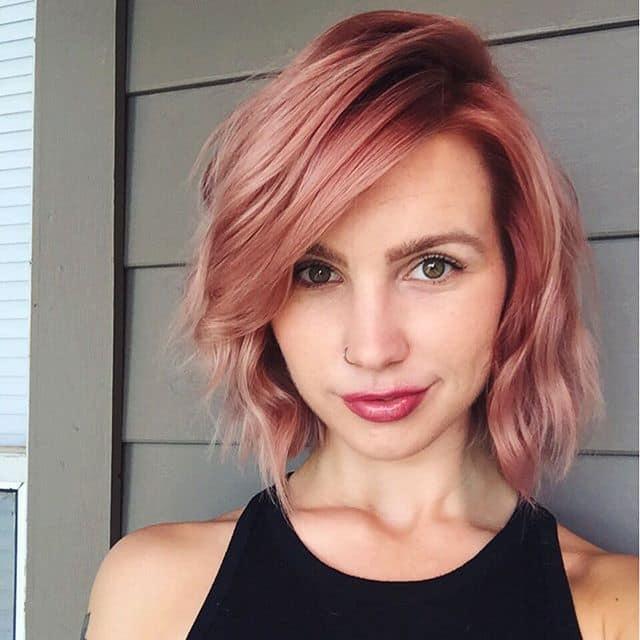 Chica con el cabello corto hasta la barbilla y teñido en color rose gold