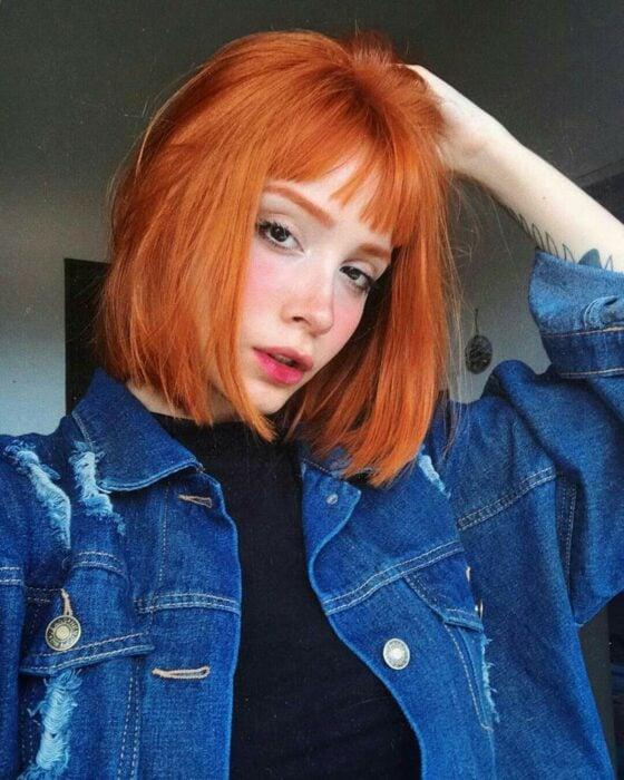 Chica con el cabello corto hasta l abarbilla y teñido en color naranja