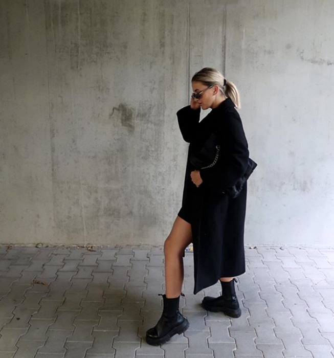 blonde girl with sunglasses, wearing short black dress, long black coat, black thick-soled boots and black handbag