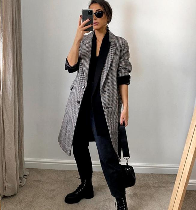 brown haired girl wearing sunglasses, black top, black jacket, long gray plaid coat, black dress pants, black chunky soled boots and mini black tote bag