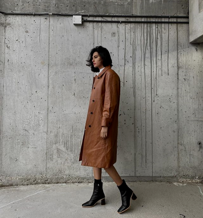 brown haired girl wearing long brown fur coat, black heeled boots with beige sole