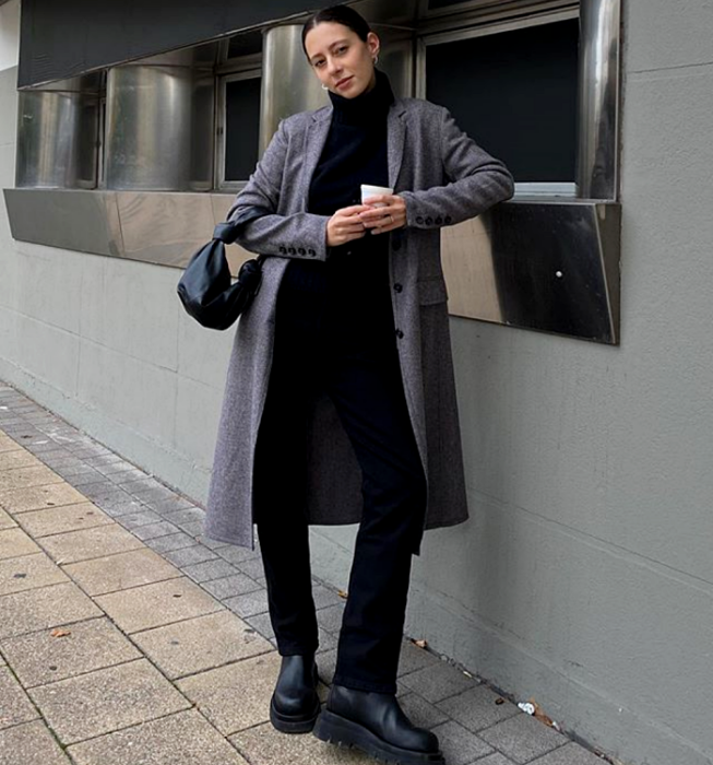brown haired girl wearing black turtleneck sweater, long gray coat, black dress pants, black leather chunky soled boots and black mini clutch bag