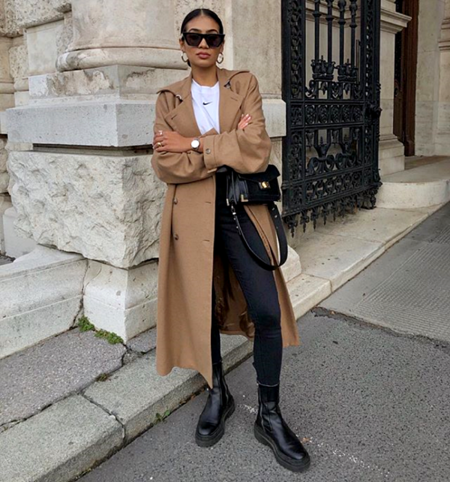 dark-haired girl wearing sunglasses, white t-shirt, brown long coat, black skinny jeans, thick-soled black leather boots and black handbag