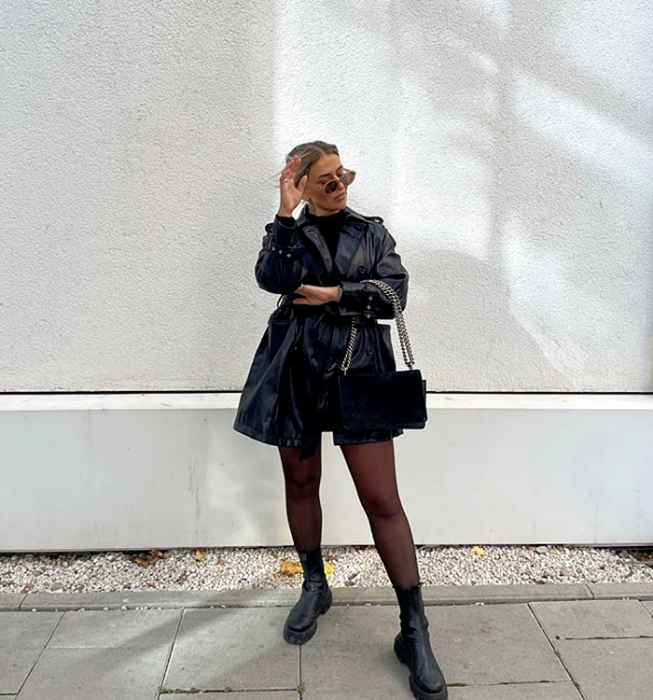 blonde girl wearing sunglasses, black turtleneck top, black mini skirt, black leather coat, black handbag with chain strap, semitransparent black stockings and leather chunky soled boots