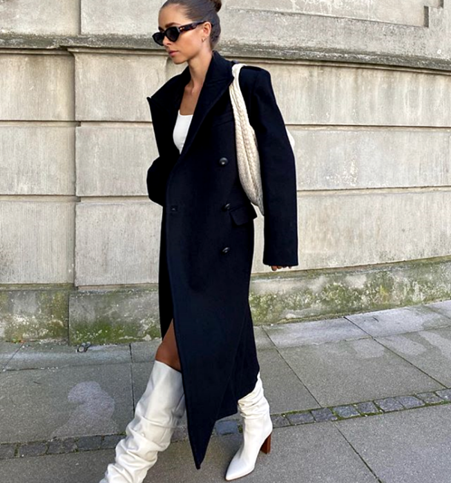 short hair girl with sunglasses, white top, long black coat, white brown high-heeled boots and white handbag