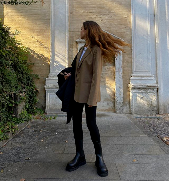 light haired girl wearing a white t-shirt, dark beige coat, black skinny jeans, black coat, and black thick-soled boots
