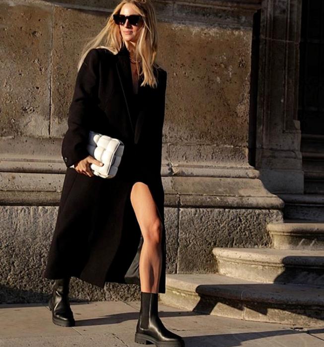 blonde girl with sunglasses, long black coat, black platform boots, black dress, white handbag