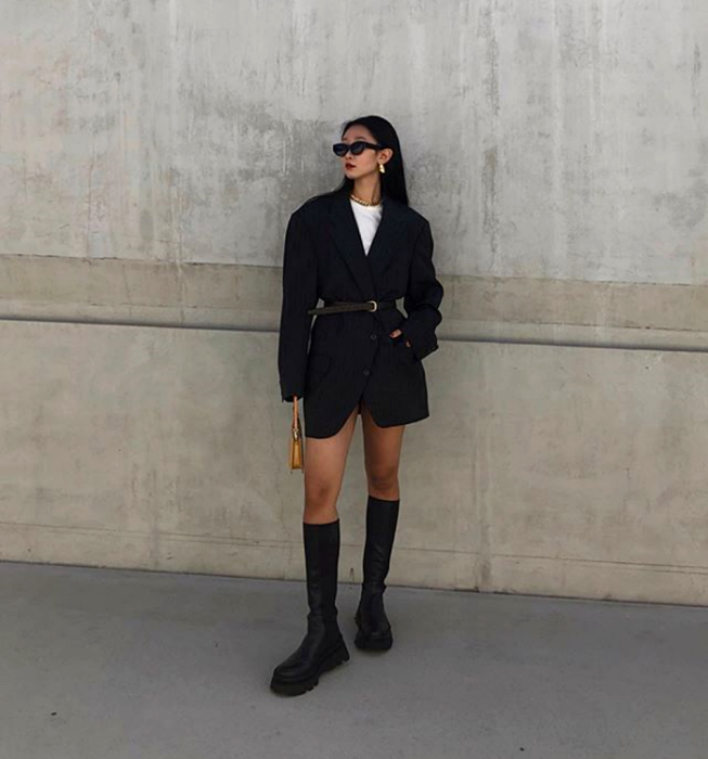 dark haired girl with sunglasses, white t-shirt, black oversized coat with belt, chunky platform long boots