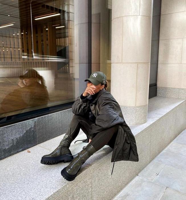 brown haired girl wearing army green cap, dark gray coat, dark gray leggings, dark gray thick soled boots