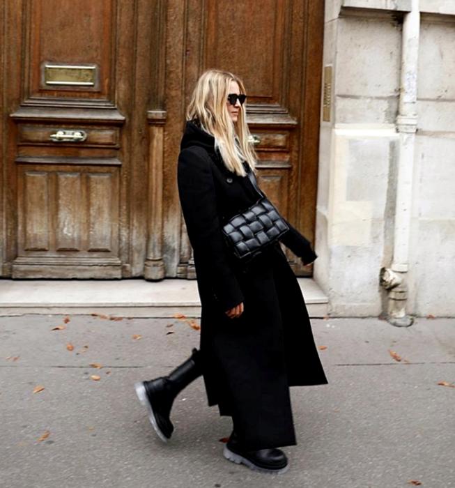 blonde girl with sunglasses, wearing a black top, black leggings, black long coat, black fur tote bag and black chunky soled boots