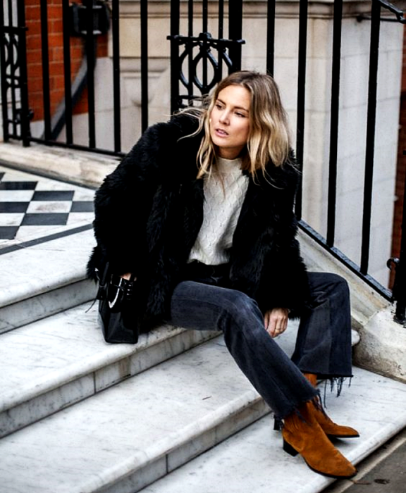 blonde girl wearing a white sweater, black plush coat, dark jeans, black handbag and brown suede velvet ankle boots