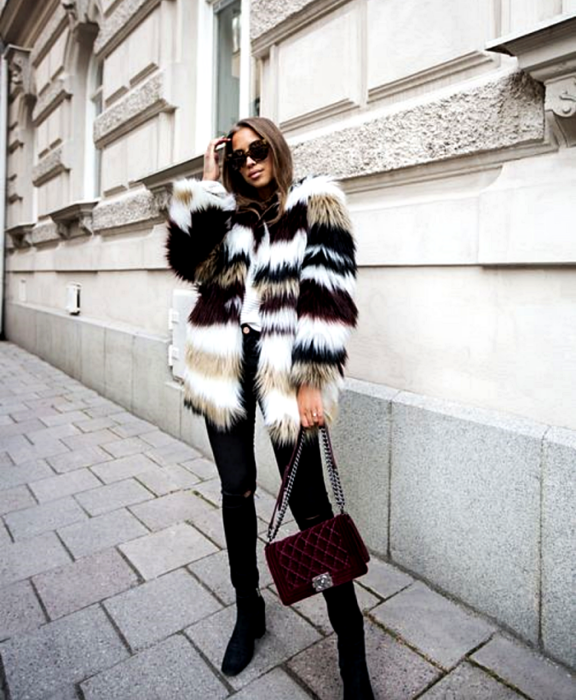 girl with light brown hair wearing sunglasses, white, black, brown and purple striped plush coat, black skinny jeans, white T-shirt, purple clutch bag and black ankle boots