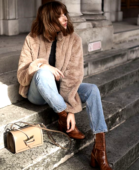 brown haired girl wearing brown plush coat, black top, blue jeans, brown leather high heel ankle boots, beige handbag