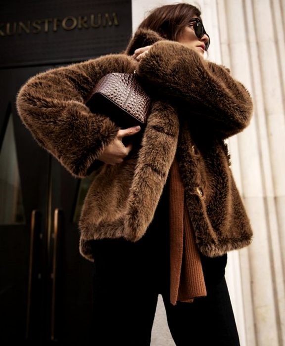 brown haired girl wearing brown plush coat, brown sweater, brown leather bag, black dress pants