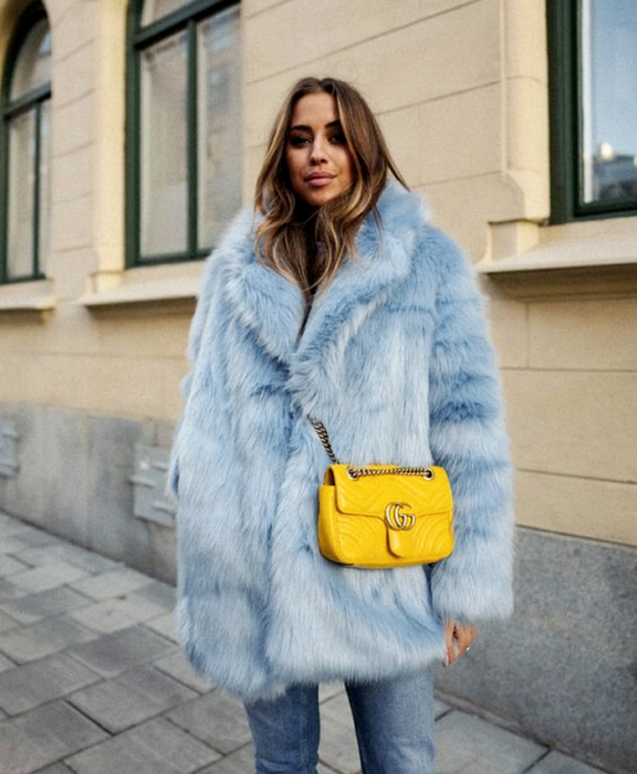 light haired girl wearing sky blue plush coat, yellow crossover bag and jeans