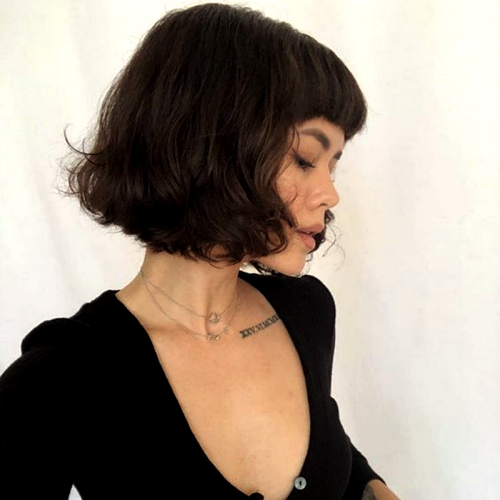 dark brown hair girl wearing french bob style haircut, french bob, black long sleeve v neck top