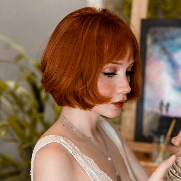 redhead girl with french bob cut, french bob, wearing beige strappy lace blouse