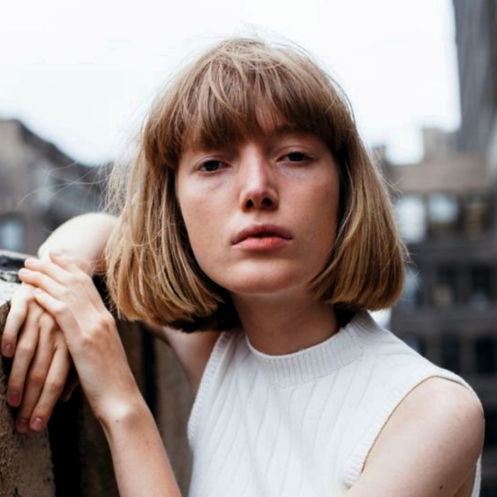 blonde girl wearing a french bob cut, french bob, with a beige turtleneck sleeveless sweater