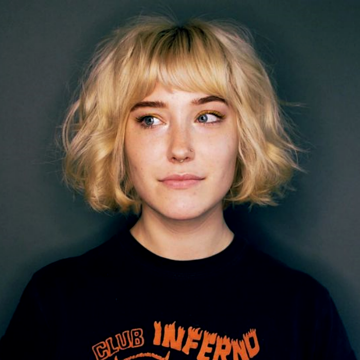 blonde girl with french bob haircut, french bob, wearing black t-shirt with orange lettering