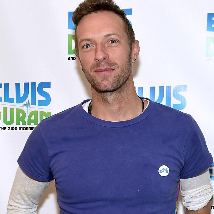 chris martin usando una camiseta azul claro de manga corta y una camiseta blanca de manga larga blanca