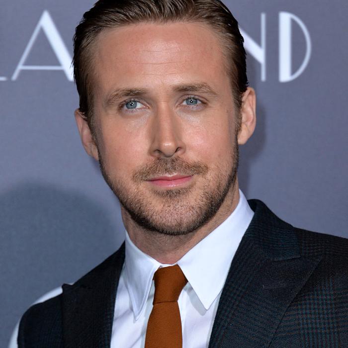 ryan gosling usando una camisa de vestir blanca con corbata naranja y saco negro con cuadros y textura