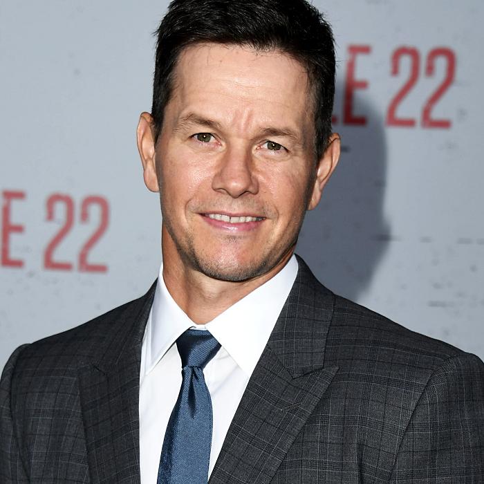 mark wahlberg usando una corbata azul, camisa de vestir blanca y saco gris oscuro de cuadros