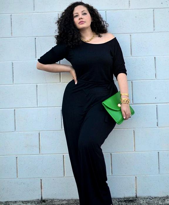 chica curvy de cabello chino usando un jumpsuit azul marino con mangas 3/4 y bolso verde de mano
