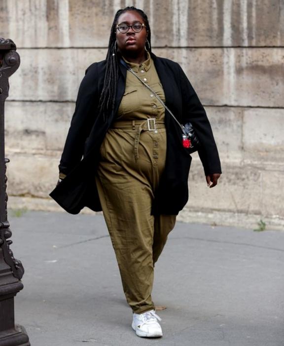 chica morena curvy usando lentes, jumpsuit verde militar con ajuste a la cintura, abrigo negro largo, bolso crossbody bag negro de piel y tenis deportivos blancos