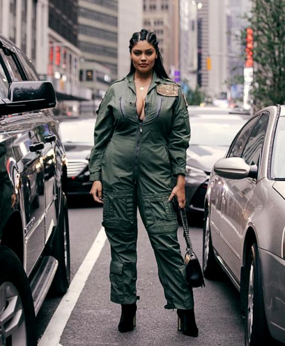 chica morena curvy usando un jumpsuit verde militar, botines negros de tacón, bolso negro de mano