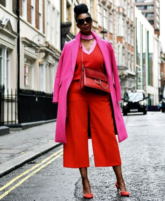 chica morena curvy usando lentes de sol, jumpsuit rojo con cuello en v, abrigo rosa largo, bolso crossbody bag rojo de piel con zapatos de tacón rojos