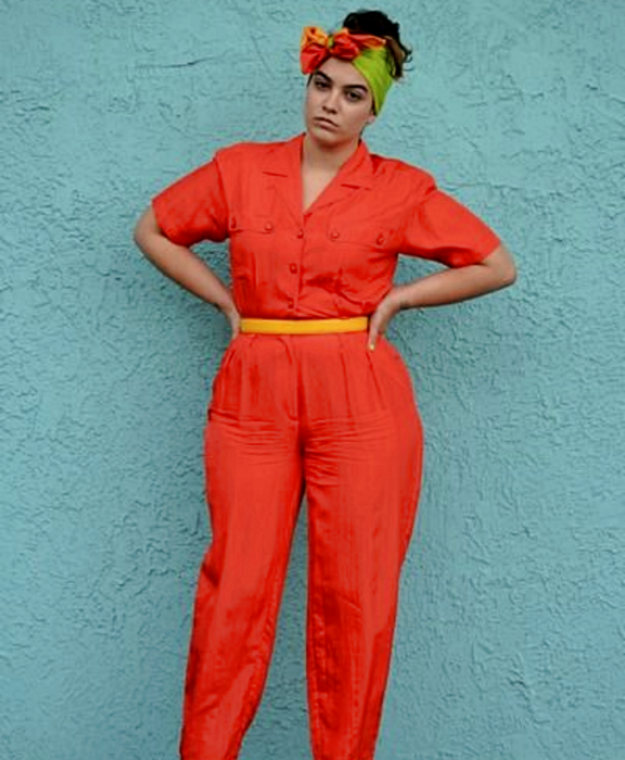 chica curvy con banda verde en el cabello, jumpsuit rojo de manga corta con cierre de botones, cinturón amarillo