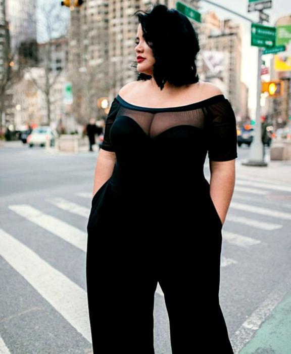 chica curvy con cabello corto usando un jumpsuit negro a los hombros con escote de corazón y pantalón largo tipo de vestir