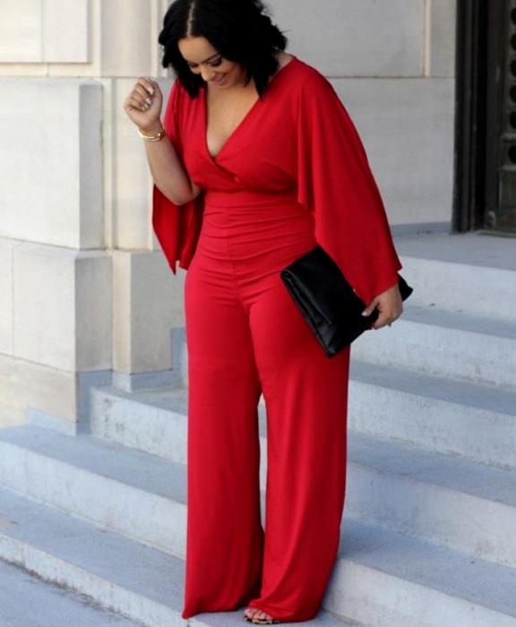 chica morena curvy usando un jumpsuit rojo con mangas holgadas largas, escote en v, pantalón largo, bolso de mano negro de piel