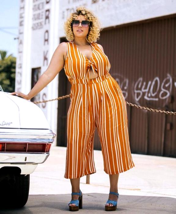 chica rubia curvy usando lentes de sol, jumpsuit naranja sin mangas con escote en v, líneas blancas, ajustado a la cintura con pantalón tipo culotte y zapatos de tacón azul