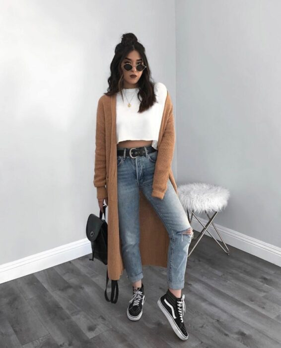 Girl wearing jeans, white top and long brown sweater